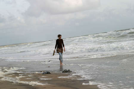 Strolling on the Beach - A young woman alone at the seashore on the Atlantic coast, France.