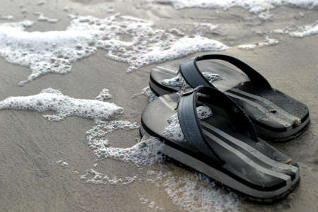 left behind: Thongs and Tide - A pair of abandoned black thongs on the sandy shoreline – the happy owner went playing in the waves…