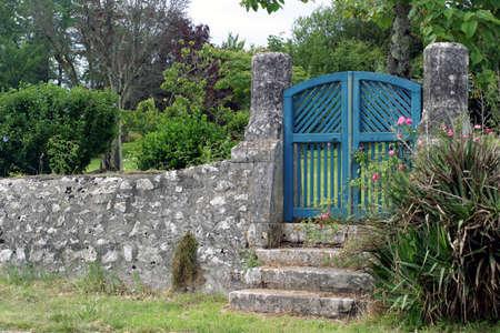 青い門 - いくつかの手順 2 つの古い石灰岩柱に囲まれた木製の庭の門に します。 写真素材