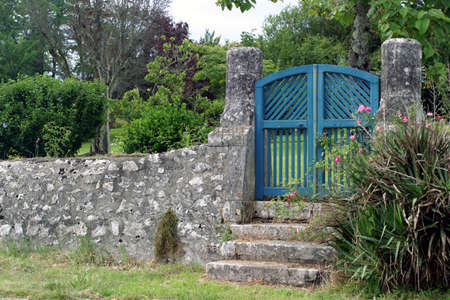wood pillars: Blue Gate - a few steps lead up to a wooden garden gate framed by two old limestone pillars. Stock Photo
