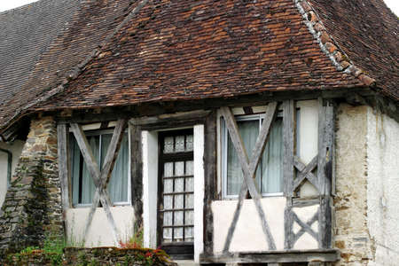Half-Timbered House - renovated Périgord Medieval home with windows inserted behind the exposed structural beams.