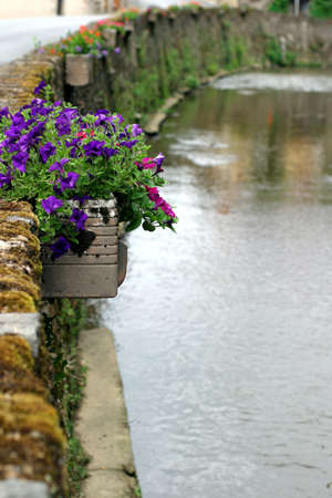 Riverside Jardiniere - charming French Perigord village with colorful petunias along the stone wall.