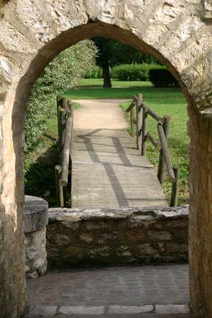 庭の入り口 - 素朴な木製の橋と小さな石の壁はこのフランスの公園での石灰岩アーチに囲まれます。