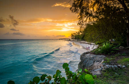 Sun goes down and paint the sky on a wonderful sunset in Barbados` beach of Miami