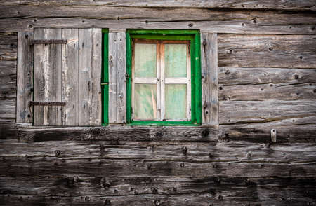 Wooden wall with green window