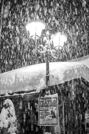 Snow covers a lamppost in an alpine village of Italian Alps.