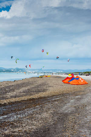 Kite surfers ride their kites in a cloudy day and fill with colors the beach Banco de Imagens
