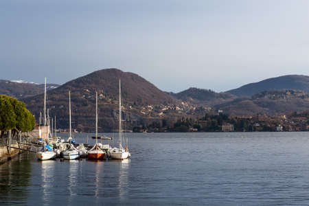 Sail boats moored along Lake Orta coast and Mottarone Hills covered of fresh snow