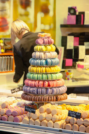 A shop window shows a tempting pyramid of tasty and colorful  macarons.