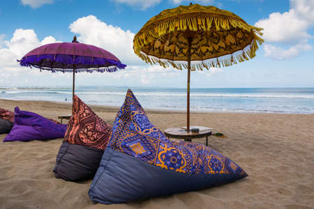 Traditional balinese umbrella and sun beds on the beach of Kuta Bali where you can relax and enjoy ocean view Banco de Imagens