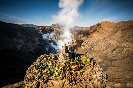 Hindu people give offerings to their god Ganesh on the crater of Bromo volcano