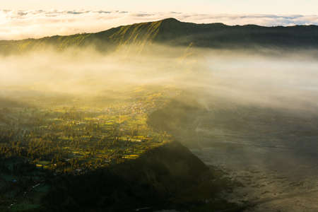 Cemorolawang is a small villagge sited on the side of Mount Bromo crater.  At sunrise clouds come from the sea and cover the village. Banco de Imagens