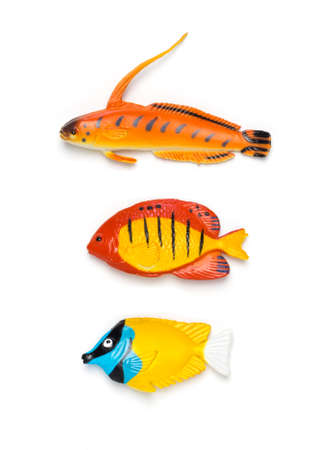 Colorful plastic fish on white isolated background