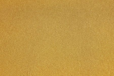 A beautifull yellow gold background from paint with glittering flakes reflecting the sunlight