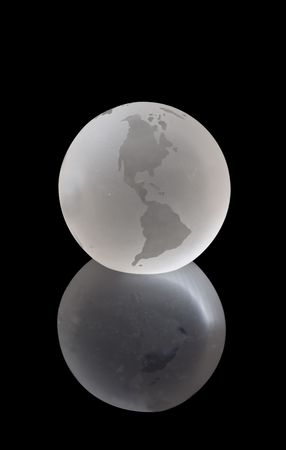 A beautiful crystal globe, our fragile planet Earth, against a black background.  Stock Photo