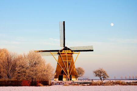 A well maintained windmill in the snow. A few minutes before sunset.