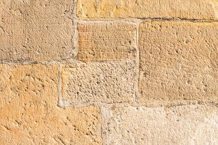 sehr alte Sandsteinmauer, die von einem Steinmetz bearbeitet wurde Standard-Bild