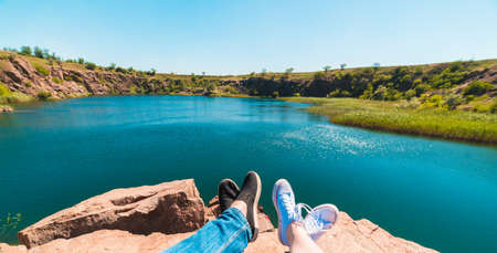 Travelers couple in sports shoes on a mountain near a river in the background of nature. Man and woman. A couple sits and makes their feet on a beautiful landscape with a river bank Stock Photo