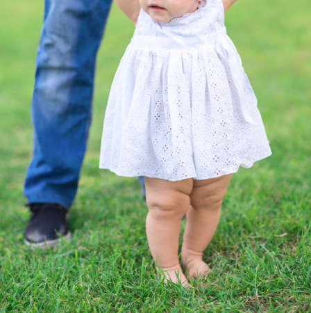 barefoot legs of a child in the green grass in the garden next to the fathers feet. concept of happy paternity. Fathers and Sons. summer