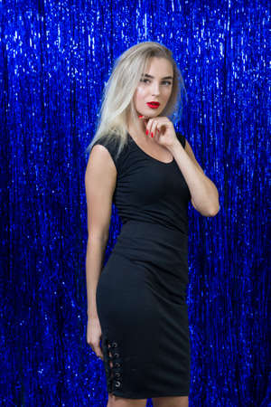 sexy blonde woman with red lipstick on lips in black dress posing on camera against the background of shiny blue pajetok, studio portrait