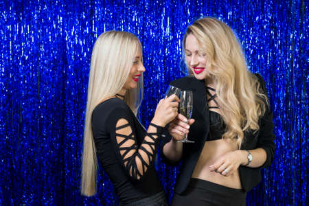 very beautiful young blondes with make-up and a hairdo in a tight-fitting figure of black clothes are having fun and having fun at a party on a blue shiny photozone Foto de archivo
