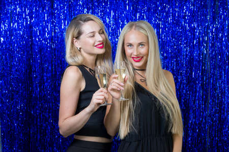 very beautiful young blondes with make-up and a hairdo in a tight-fitting figure of black clothes are having fun and having fun at a party on a blue shiny photozone.