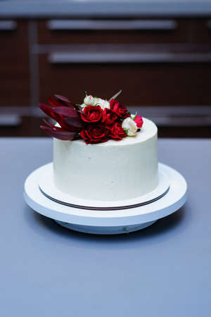 Decorated by flowers white naked cake, rustic style for weddings, birthdays and events. Stock Photo
