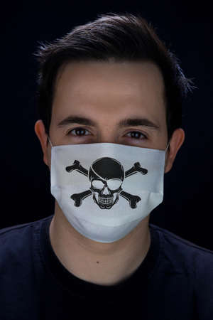 Man in a mask for protection with a print Jolly Roger Corona Virus Covid-19 版權商用圖片