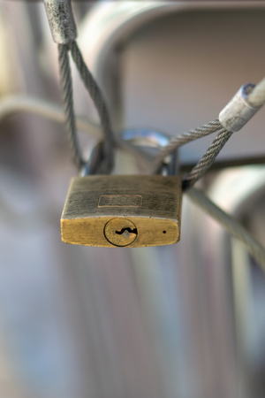 Closed padlock attached to three steel wire ropes. Close up. Blurred background.