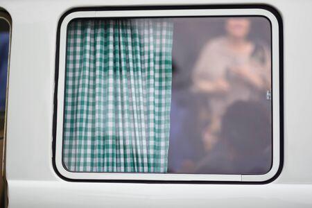 White window with green plaid curtains. Windowpane.