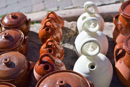 White earthenware pitchers and pots in a market in Spain. Handmade pottery. Workshop.
