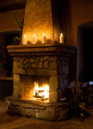 stone fireplace: Fireplace room. Chimney, candles and woodpile. Chimney place. Stock Photo