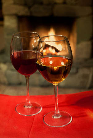 cosiness: Two glasses of wine. Red tablecloth. Fireplace. Chimney. (vintage paper background, retro style).