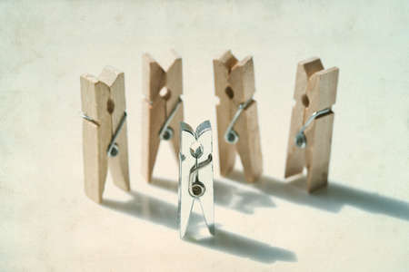 Clothespins. Playground people. Abstract. Opposition. Different type of objects. Vintage paper background. Soft focus.