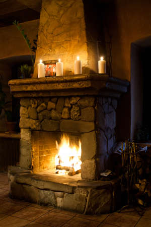 Fireplace room. Chimney, candles and woodpile. Chimney place. Vintage style.