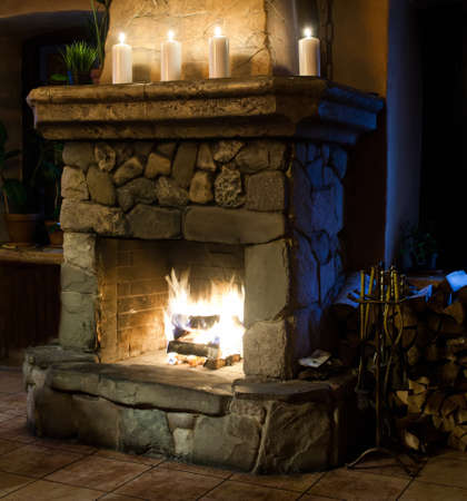 stone fireplace: Fireplace room. Chimney, candles and woodpile. Chimney place. Vintage style.
