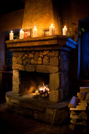 Fireplace room. Chimney, candles and woodpile. Chimney place. Stock Photo