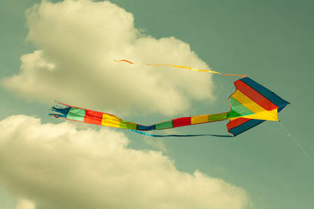 pirouette: Multicolor kite flying in the cloudy sky. Retro style. (Toned photo.) Stock Photo