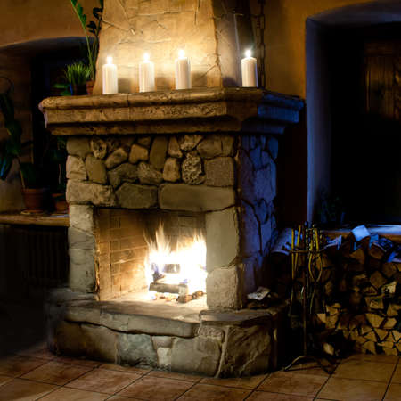 wood burning: Fireplace room. Chimney, candles and woodpile. Chimney place. Stock Photo