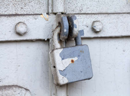 attrition: Vintage (retro) metal lock on a gray door. Classic hanging lock. Attrition, old paint and dirt. Soft focus.