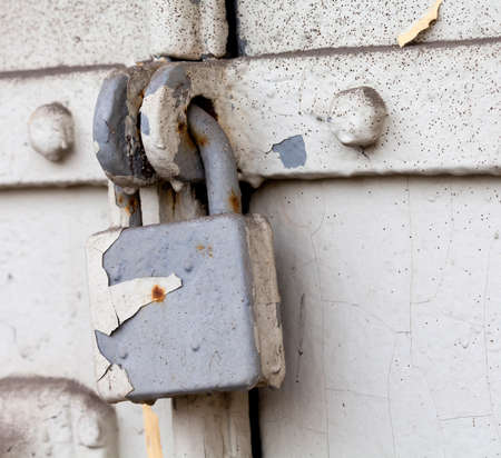 flawed: Vintage (retro) metal lock on a gray door. Classic hanging lock. Attrition, old paint and dirt. Soft focus.