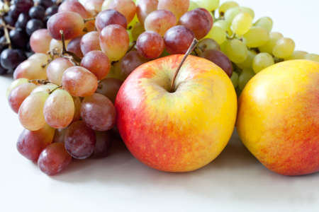 Apples and grapes on a white background. Thanksgiving day. Harvest. Fruit set: red and yellow apples and green, blue and purple grapes. Stock Photo