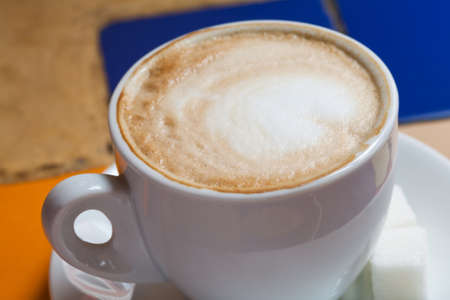 approximation: Cappuccino in a white cup. Close-up. Cup of coffee with milk.