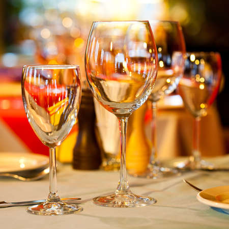 Hotel service: table in a restaurant with a white tablecloth, red napkins, wine glasses and cutlery. photo