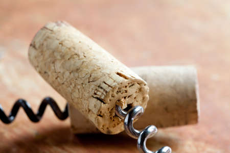 Two corkscrew with wine corks. Macro view. Closeup. Soft focus. Retro style. Paper texture background. photo