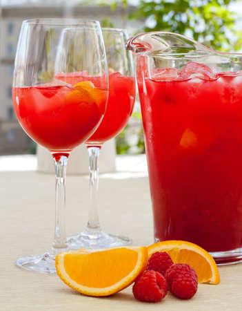 Raspberry Lemonade: two glasses, pitcher, raspberries on the table. Sunshine. shadows. white wooden table. photo