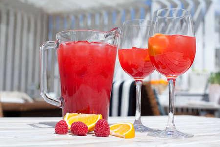 limonada: Raspberry Lemonade: dos vasos, lanzador, frambuesas en la tabla. Sol. sombras. mesa de madera blanca.
