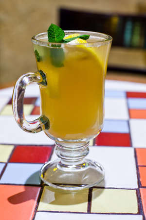 Ginger tea in a glass cup on a mosaic table. (soft focus) photo