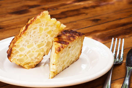 spanish onion: Spanish omelet on a white plate. The plate on the wooden table. Spanish omelette with potatoes and onion. Tortilla espanola (wooden table background).