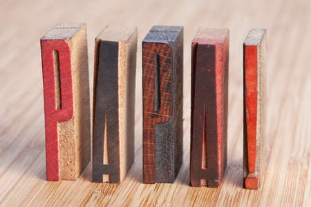 Papa written with colored vintage letterpress (wooden background). Retro vintage letterpress type. (Soft focus) photo